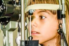 Litlle girl taking the eye exam test Royalty Free Stock Photos