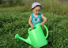 Litlle girl and watering-pot. Litlle girl in clover meadow Royalty Free Stock Photography