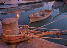 Litlle woden boats. Night view on a little rust wooden boat, and a small submerged boat, mooring detail and reflection of a big tourist wooden boat anchored in a Royalty Free Stock Photos
