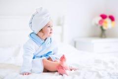 Litlte flicka i en badrock och en handduk Arkivfoto