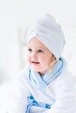 Litlte flicka i en badrock och en handduk Royaltyfri Fotografi