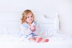 Litlte flicka i en badrock och en handduk royaltyfria bilder