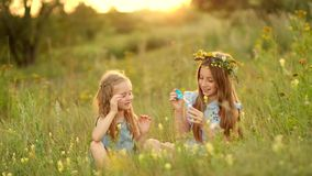 Litlte Girls Blowing Bubbles. Little girls are blowing bubbles and laughing on the summer meadow with high grass stock footage