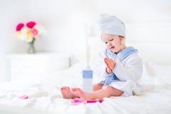 Litltemeisje in een badjas en een handdoek Stock Foto's