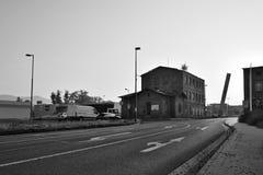 Litomerice,捷克共和国- 2018年5月19日:导致在老历史工厂厂房和停放的汽车附近的柏油路shopp 免版税库存照片