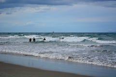 Litorais de Nova Zelândia; seascape bonito, oceano azul brilhante, e alguns povos não identificados que apreciam longe atividades imagem de stock royalty free