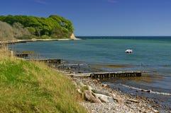 Litoral Báltico com praia, o barco ancorado e o penhasco arborizado Imagem de Stock