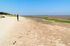 Litoral com o polo da praia com parte superior vermelha e pegadas na areia, N Imagens de Stock Royalty Free