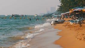 Litoral da praia Os povos banham-se no mar, molham os passeios, batida da onda na costa arenosa tailândia Pattaya filme