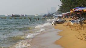 Litoral da praia Os povos banham-se no mar, molham os passeios, batida da onda na costa arenosa tailândia Pattaya vídeos de arquivo