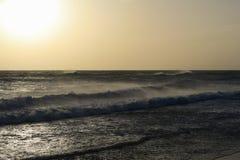 Litoral espanhol bonito: Praia, mar, ondas com crista branca durante o por do sol imagem de stock royalty free