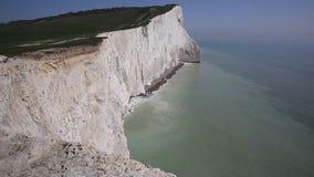 Litoral inglês bonito Seaford Sussex do leste Inglaterra Reino Unido com os penhascos de giz brancos, as ondas e o céu azul filme