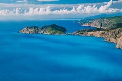 Litoral na frente da vila de Assos e Frourio peninsular Baía azul leitosa bonita com o costline rochoso marrom da pedra calcária foto de stock