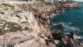 Litoral rochoso com as ondas fortes tormentosos que batem penhascos e espirro Tiro aéreo do zangão da praia rochosa coral com col vídeos de arquivo