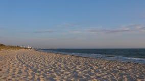 Litoral vazio com ondas e cidade no horizonte e no céu azul bonito vídeos de arquivo