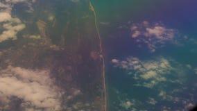 Litorale di vista sotto le nuvole dalla finestra dell'aereo di linea video d archivio