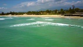 litorale di volo dell'Uccello-occhio ed oceano di azzurro con i surfisti stock footage