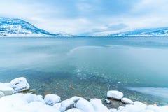 Litorale roccioso, acqua blu calma e montagne nella distanza con le nuvole di tempesta Fotografie Stock Libere da Diritti