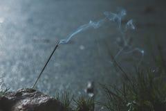 Liträucherstäbchen, die in einem Naturstein mit Oberteildruckammoniten, Rauch stehen lizenzfreie stockfotografie