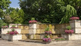 Lits de fleur colorés et fontaine en pierre à l'entrée de Dallas Arboretum et du jardin botanique photo libre de droits