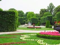 Lits de fleur idéaux abstraits et arbres tondus en parc soigné photographie stock libre de droits