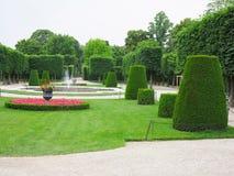 Lits de fleur idéaux abstraits et arbres tondus en parc soigné images stock