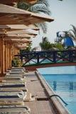 Lits de planche sous des parapluies à la piscine dans l'hôtel Égypte Photographie stock libre de droits