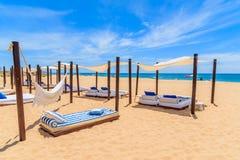 Lits de Sun sur la plage sablonneuse dans la ville de Salema Images libres de droits