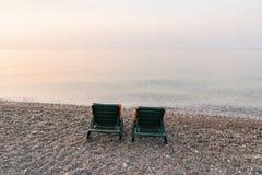 Lits en plastique du soleil avec les caps oranges sur la plage de mer au lever de soleil Concept de vacances d'?t? images stock