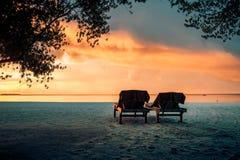 Lits pliants à l'arrière-plan tropical de plage de coucher du soleil Photos stock