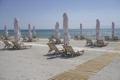 Lits pliants avec les parapluies fermés sur une plage avec le sable Photos libres de droits