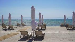 Lits pliants avec les parapluies fermés sur une plage avec le sable clips vidéos