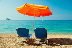 Lits pliants bleus et parapluie orange (parasol) sur la plage de paradis dedans Images libres de droits