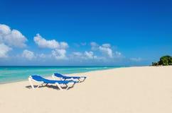 Lits pliants bleus sur la plage des Caraïbes arénacée Photos libres de droits