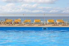 Lits pliants de piscine autour d'une piscine photo stock