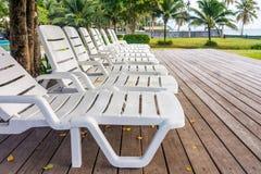 Lits pliants en plastique blancs sur la plate-forme en bois dans le jardin Image libre de droits