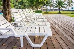 Lits pliants en plastique blancs sur la plate-forme en bois dans le jardin Photos libres de droits