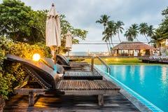 Lits pliants et parasols en bois sur la piscine voisine de plate-forme en bois Photos stock