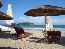 Lits pliants sur la plage avec le sable blanc photos stock