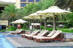 Lits pliants vides par la piscine de station de vacances Photos stock