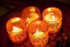 Litstearinljus i dekorerade exponeringsglas på plattan som beskådas från över Royaltyfri Fotografi