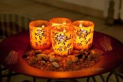 Litstearinljus i dekorerade exponeringsglas på plattasidosikt Royaltyfri Bild
