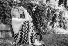 Litt?rature ennuyeuse La femme a fatigu? la coupure blonde de prise de visage d?tendant dans le livre de lecture de jardin L'?tud image stock