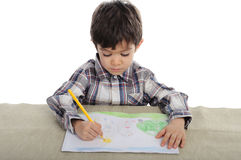 Litte boy is drawing with pensils Royalty Free Stock Image