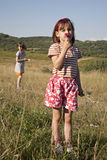 Litte girl by play on meadow Stock Images