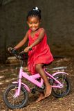 Littel african girl on bicycle. Royalty Free Stock Images