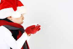 Littel boy in santa claus hat and scarf and gloves blowing snowflakes Stock Images