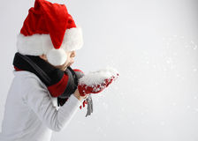 Littel boy in santa claus hat and scarf and gloves blowing snowflakes Royalty Free Stock Photo