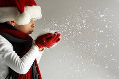 Littel boy in santa claus hat and scarf and gloves blowing snowflakes Stock Photos