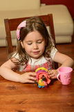 Littel girl playing indoor with clay Stock Image